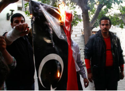 Protestors burn a flag belonging to the Libyan Embassy to protest the death of an Egyptian Christian suspected of proselytizing in Libya. (Ahramonline)