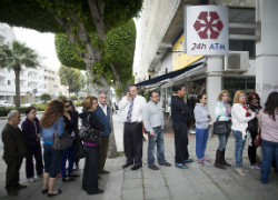 Customers stand in line to withdraw cash from an automated teller machine (ATM) outside a Cyprus Popular Bank Pcl. (PBS)