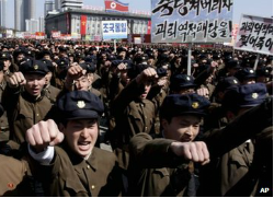 University students punch the air as they march through Kim Il Sung Square in downtown Pyongyang, North Korea (BBC)