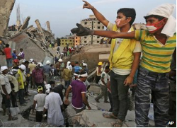 Bangladeshi rescuers from a youth group gesture for help at the site of a building that collapsed in Savar, near Dhaka, Bangladesh. (BBC)