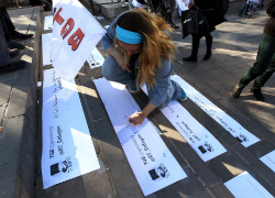 A woman protests the Twitter ban by writing a physical tweet. Image Source: Adem Altan/AFP/Getty Images.