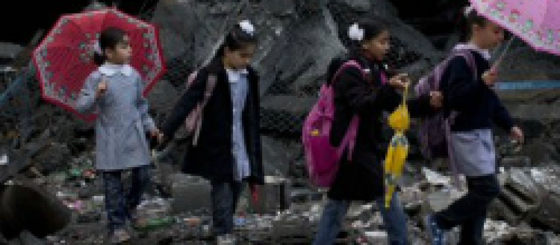 Schoolchildren walk in debris by a damaged school in Gaza City. (Huffington Post)