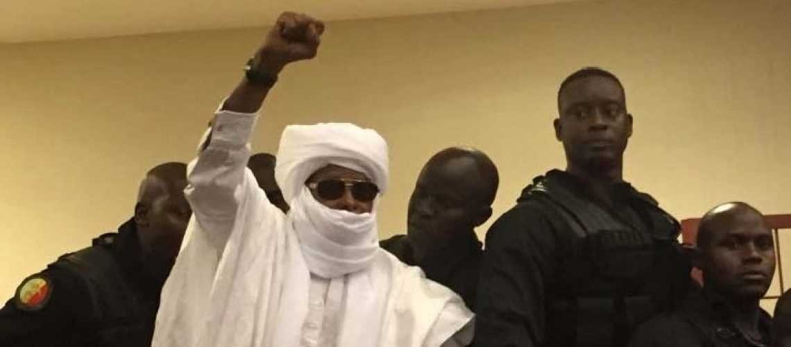 Chad's former dictator Hissene Habre raises his hand during court proceedings in Dakar, Senegal, Monday, May 30, 2016. Judge Gberdao Gustave Kam declared Habre guilty and sentenced him to life in prison for crimes against humanity, war crimes and torture, in a packed courtroom, Monday.(AP Photo/Carley Petesch)