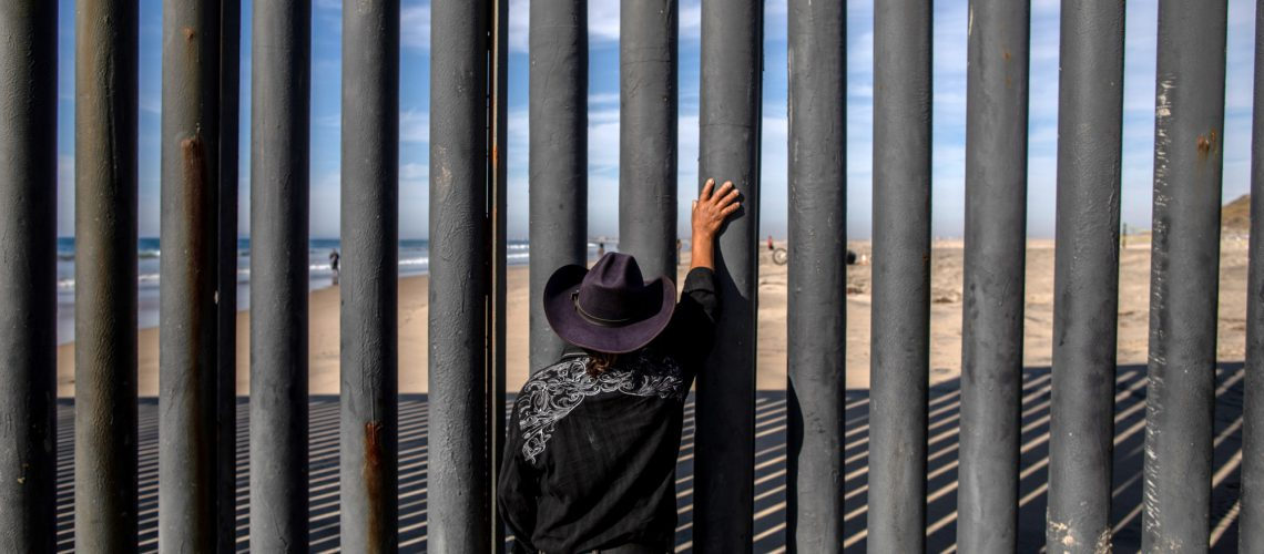 A man looks towards the United States through a fence in Tijuana, Mexico.