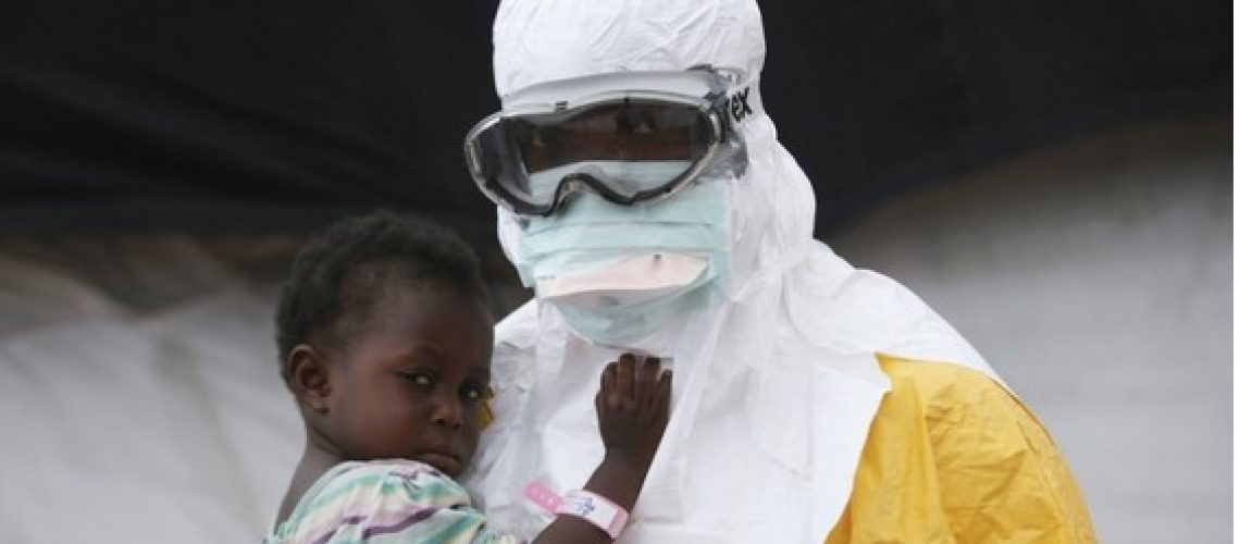 An MSF health worker in protective clothing holds a child suspected of having Ebola in the MSF treatment center in Paynesville, Liberia, October 2014. From (Doctors without borders)