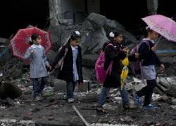 Schoolchildren walk in debris by a damaged school in Gaza City. (Huffington Post)
