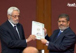 Egypt's President Mohammed Mursi receives the draft constitution from the Constituent Assembly. (Al Arabiya)